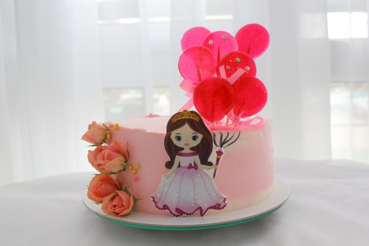 Girl with sugar balloons. Princess cake. Biscuit covered with pink cream cheese frosting, roses and sugar beads.