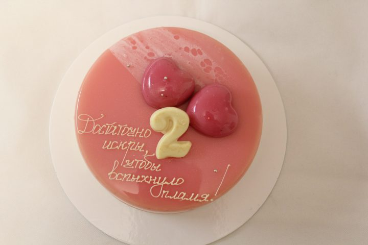 Two red hearts on a pink mirror glaze. Lovers cake, tenderness and beauty.