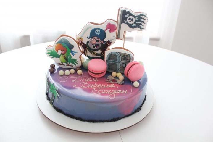 Pirate cake idea. Mirror glaze cake of a water-color effect with gingerbread figures of a fat one-eyed captain, parrot, treasure chest, sugar pearls and macarons.