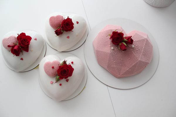 Heart shaped cake covered with white mirror glaze and pink velvet textures and decorated with scarlet live roses on top.