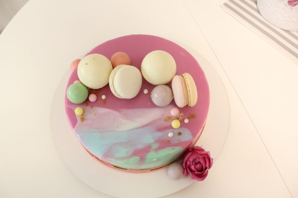 Awesome pink mirror glaze cake with three water-color smear. This romantic cake comes with m'n'ms, macaron, sugar bubbles at the top and a rose bud at the base.