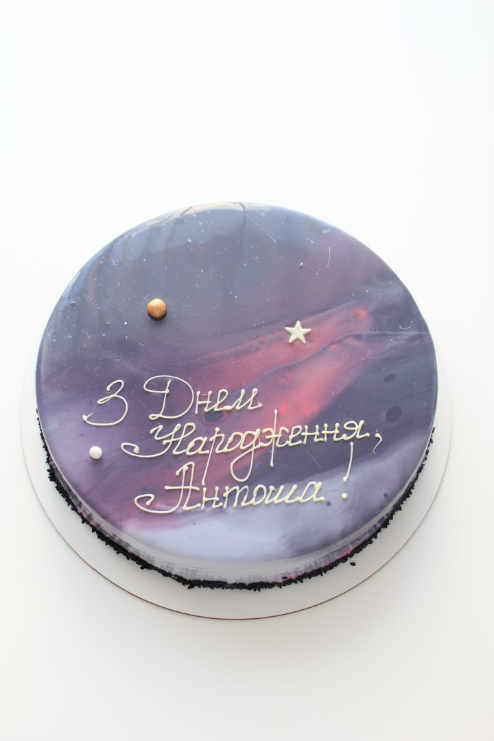 Beautiful and mysterious galaxy nebula cake. Dazzling mirror glaze of cosmic colors decorated with small planet and star from sugar.