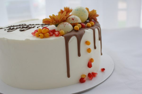 A perfect romantic cake for husband. Covered with cream cheese frosting. Sea buckthorn, garnet, bubbles from white chocolate and a flower on top.