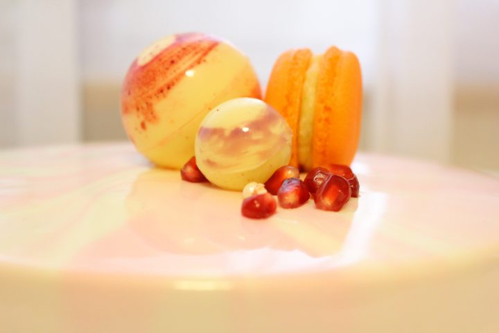 Orange cake. With white sugar beads on a pink smoky mirror glaze. Chocolate balls, macaron and pomegranate grains.