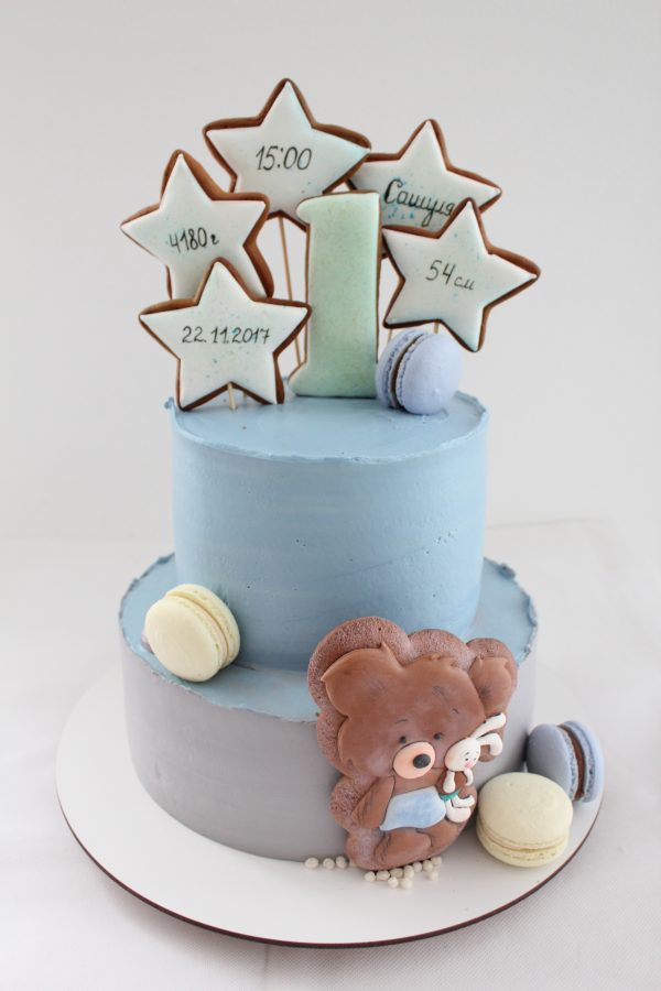 Two-tier cream cheese frosting cake of blue and grey colors. Dessert with macaron and gingerbread stars at the top, and figure of a bear hugging bunny at the bottom. Cute first birthday cake idea.