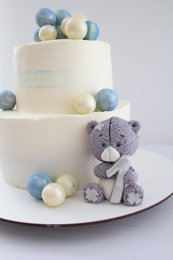 Cute vintage Teddy Bear cake. A toy with number One. Two-tier biscuit cake with cream cheese frosting. Colored balls from white chocolate.
