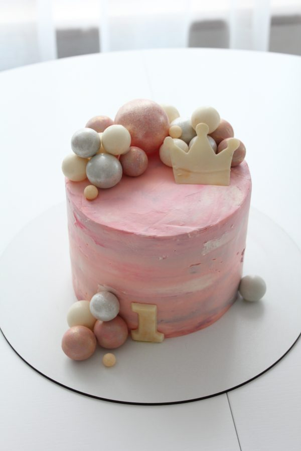 """Bubble cake for child's first birthday. Multi-color cream cheese frosting of a water-color effect. Big """"1"""" at the bottom, sugar crown and chocolate balls of various size at the top."""