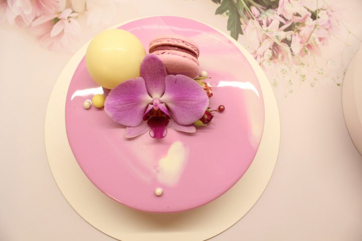 Amazing and tender orchid cake. Mirror glaze of a smoky pink color decorated with macaron, bubbles from white chocolate and purple flower in a center.